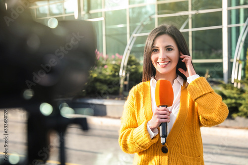 Foto Young female journalist with microphone working on city street