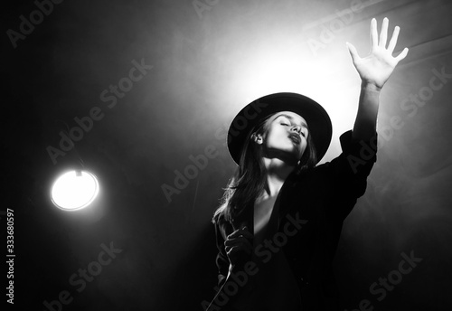 Beautiful braless actress girl, wearing an unbuttoned blazer and a hat, poses and dances in the warm light rays of scenic illuminators in the theatrical fog Canvas-taulu