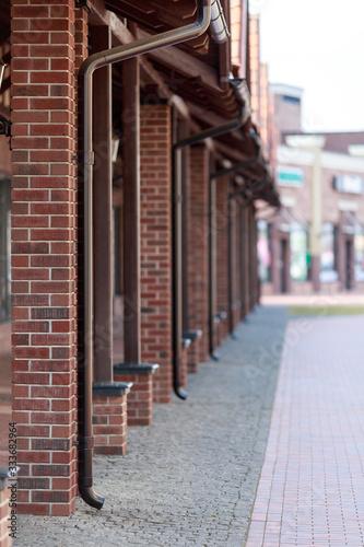 Vászonkép red brick columns drainpipe street europe
