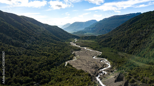 Photo Aerial view on green valley with river stream surrounded by mountains
