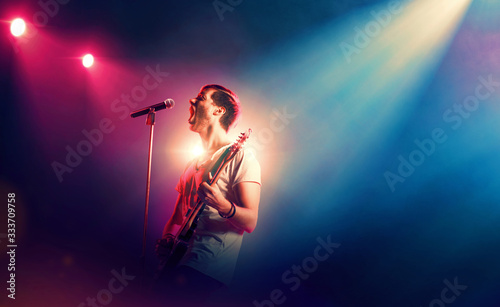 Fotografie, Tablou Singer with a guitar performing on a stage