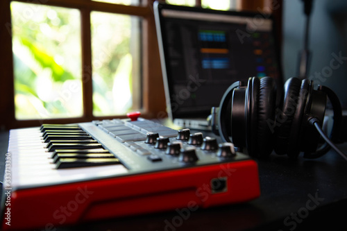Obraz na plátně Midi keybard in a music producer home studio, desk with headphones and a notebook