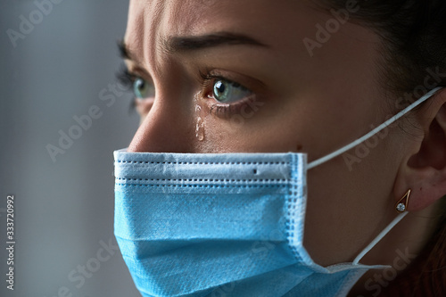 Upset depressed melancholy sad crying woman in protective face mask with tears eyes during serious illness, coronavirus outbreak and flu covid-19 epidemic Fototapet