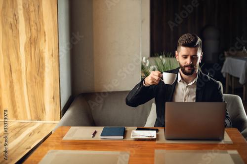Vászonkép Caucasian adult bearded man indoors in cafe