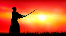Japanese Warrior Samurai With A Sword At Sunset. A Man Stands With A Sword In His Hands Against The Backdrop Of A Sunny Sunset