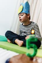 Niño De 5 Años Celebra Su Cumpleaños Durante El Confinamiento Coronavirus Covid19, Juega Con El Pastel Y La Vela, Lleva Corona Hecha A Mano, Camiseta A Rayas Y Chandal Azul Oscuro. Es  Caucásico.