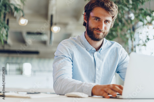 Fotografiet Businessman in shirt working on his laptop in an office