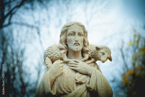 Fototapeta Ancient stone statue of Jesus Christ Good Shepherd with the lost sheep on his shoulders