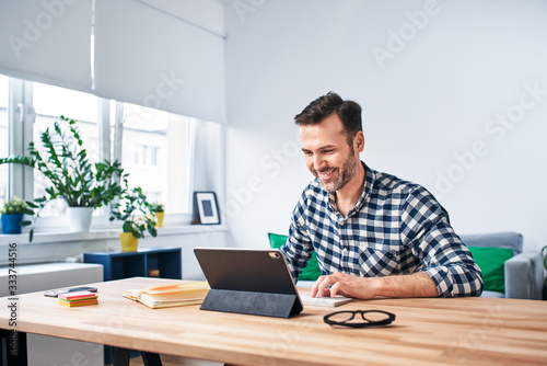 Obraz Freelancer working from home sitting at desk with digital tablet - fototapety do salonu