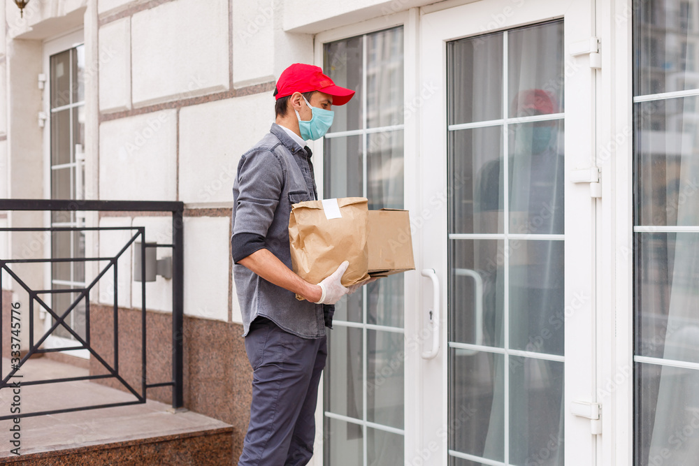 Fototapeta Courier in protective mask and medical gloves delivers takeaway food. Delivery service under quarantine, disease outbreak, coronavirus covid-19 pandemic conditions.