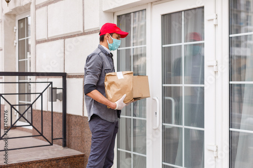Fototapeta Courier in protective mask and medical gloves delivers takeaway food. Delivery service under quarantine, disease outbreak, coronavirus covid-19 pandemic conditions. obraz