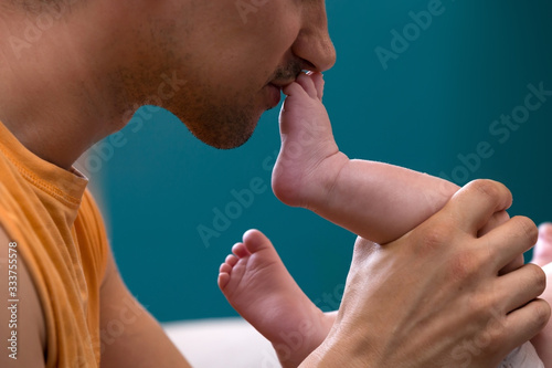 Tela Proud Father Kissing His Newborn Baby's Foot