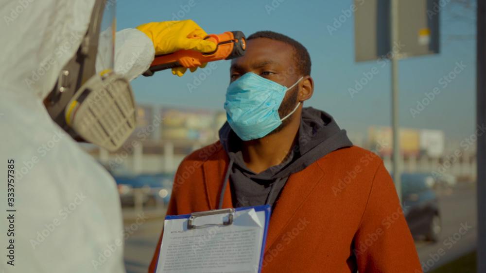 Fototapeta Near airport screening of passengers travellers african american man Covid-19 coronavirus symptoms temperature checkpoints mask infection epidemic corona passengers slow motion