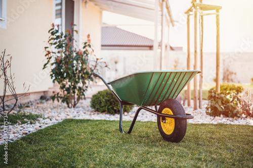 Green wheelbarrow in the garden Fotobehang