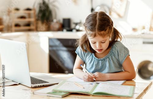Fotografia Little schoolgirl doing homework at home