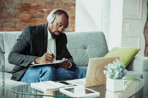 Obraz Businessman or student working from home being isolated or keep quarantine 'cause of coronavirus. African-american man using laptop, tablet and headphones. Online conference, lesson, remote office. - fototapety do salonu