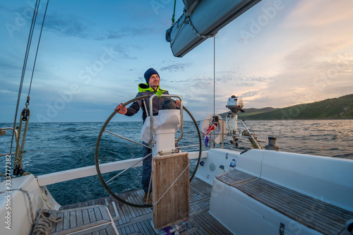 Fotografía Sailboat helmsman at his watch with beautiful sunset near Campbeltown, Scotland