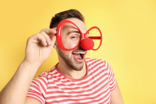 Emotional Young Man With Party Glasses And Clown Nose On Yellow Background. April Fool's Day