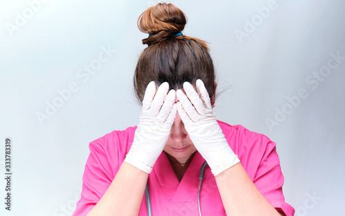 Tired, worried nurse with a pink uniform Fototapet