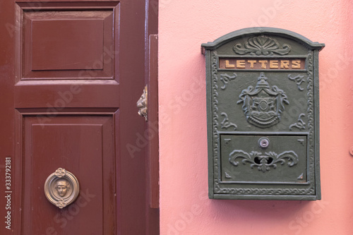 A bright retro looking green mailbox, or letterbox, affixed to the exterior wall of a pink house Canvas Print