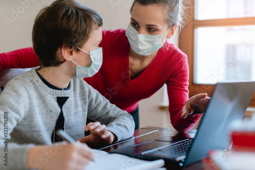 Mother and son in video chat with teacher wearing masks