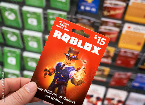 Roblox gift card in a hand over gift cards background Stock Photo