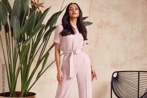 Beautiful sexy brunette woman tanned skin face cosmetic makeup wear pink suit pants for date walk office fashion clothes style collection interior room sand color safari summer armchair palm boho.