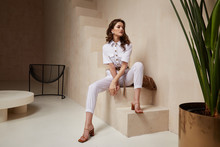 Beautiful Woman Fashion Model Brunette Hair Tanned Skin Wear White Overalls Button Suit Sandals High Heels Accessory Bag Clothes Style Journey Safari Summer Collection Plant Flowerpot Wall Stairs.