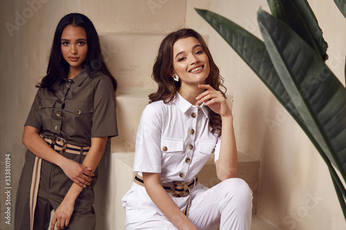 Fotografía Two beautiful woman fashion model brunette hair friends wear overalls suit casual style sandals high heels accessory clothes safari Sahara journey summer hot collection plant flowerpot wall stairs