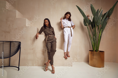 Fotomural Two beautiful woman fashion model brunette hair friends wear overalls suit casual style sandals high heels accessory clothes safari Sahara journey summer hot collection plant flowerpot wall stairs