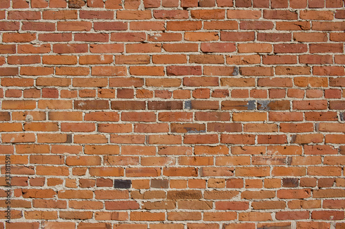 Shabby chic old brick wall texture background with deteriorating bricks in colors of red and orange