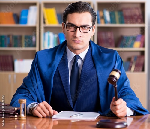 Photo Handsome judge with gavel sitting in courtroom