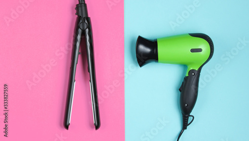Minimalistic beauty and fashion still life. Hair dryer, hair straightener on colored pastel background. Top view, flat lay