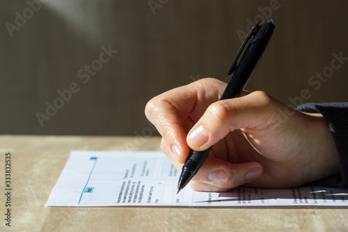 Closeup of woman's hand holding a pen filling out a census form. Canvas-taulu
