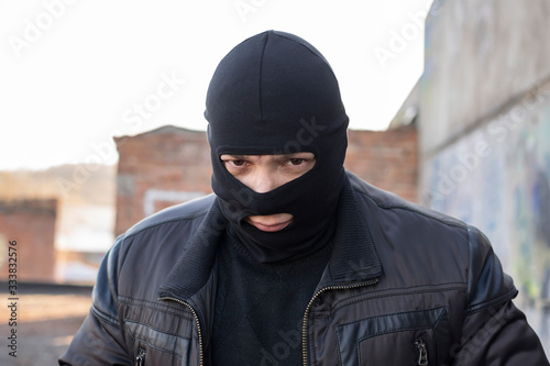 Fotomural a bandit, a terrorist in a black mask and jacket in a slum and on the territory