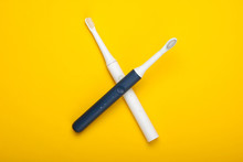 Two Modern Electric Toothbrushes On Yellow Background. Top View. Teeth Care. Minimalism