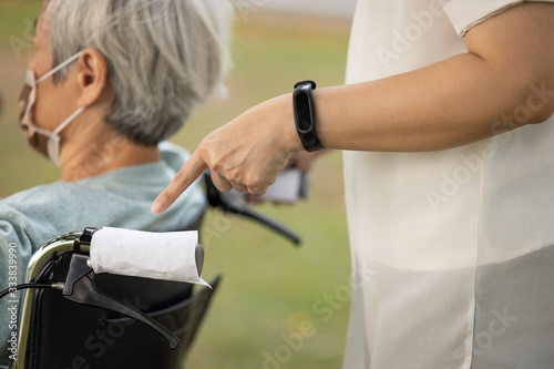 Vászonkép Hand of asian girl using tissue paper entwine handlebar of wheelchair instead of