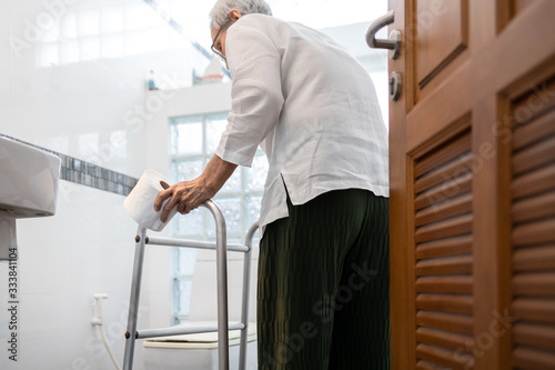 Valokuva Senior woman with diarrhea holding tissue roll near a toilet bowl,elderly have a