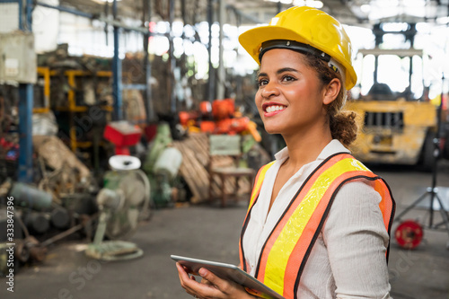 Canvastavla Female industrial worker working and checking machine in a large industrial factory with many equipment
