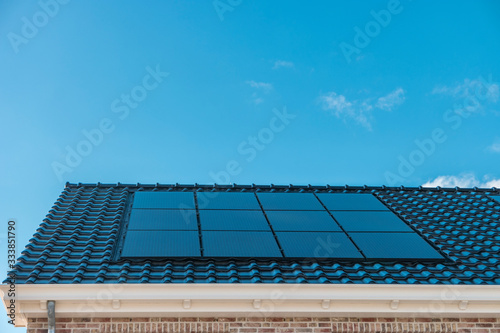 Fototapeta Newly build house in the Netherlands with solar panels attached on the roof against a sunny sky Close up of new building black solar panels obraz