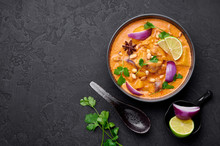A Chicken Massaman Curry In Black Bowl At Dark Slate Background. Massaman Curry Is Thai Cuisine Dish With Chicken Meat, Potato, Onion And Many Spices. Thai Food. Copy Space. Top View