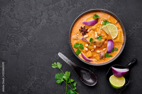 Obraz A Chicken Massaman Curry in black bowl at dark slate background. Massaman Curry is Thai Cuisine dish with chicken meat, potato, onion and many spices. Thai Food. Copy space. Top view - fototapety do salonu