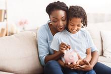 African American Family Inserting Money Into Piggybank