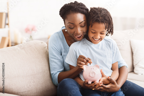 Fotografie, Obraz African american family inserting money into piggybank