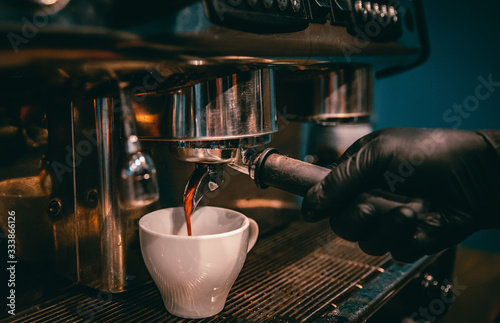 Fotografie, Obraz coffee machine is pourig coffee to white cup in bar