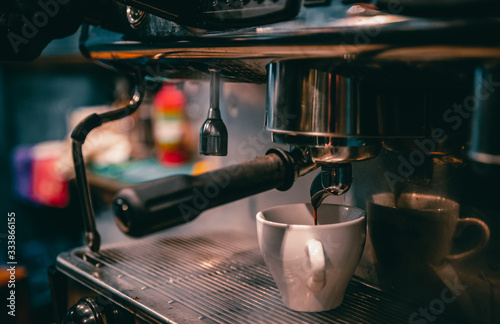 Fototapeta coffee machine is pourig coffee to white cup in bar