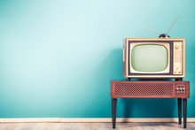 Retro Old Outdated Classic Television Receiver With TV Antenna From Circa 60s Of XX Century On Wooden Stand With Amplifier Front Gradient Mint Blue Wall Background. Vintage Style Filtered Photo