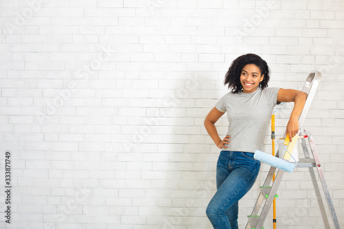 Woman beside stepladder with roller in hand on white brick wall background Wallpaper Mural
