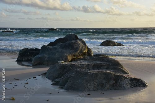Photo Large Rock in the Sand and Waves Rolling Ashore