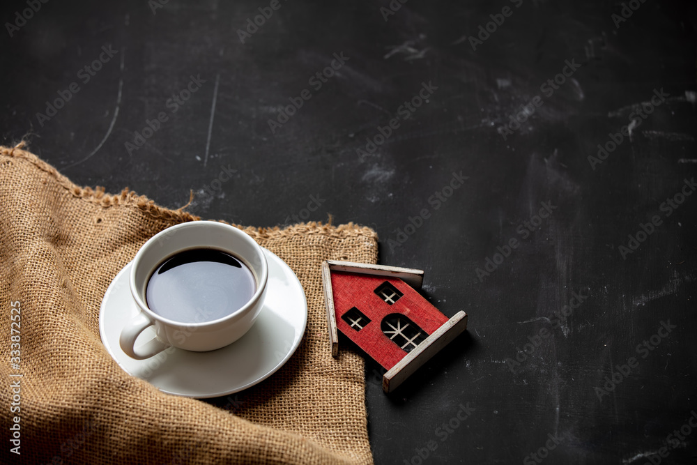 Fototapeta White cup of coffee and little house on dark background
